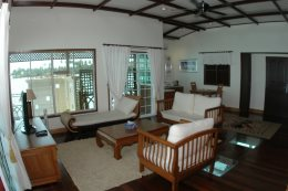 Bougain Villa Suite has a spacious living room with a balcony view of Sipadan Island, and glass floor view of the ocean below.